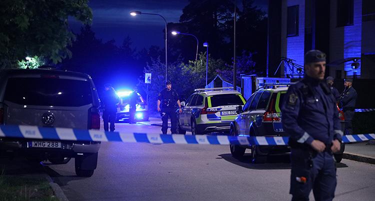 Det är mörkt ute. Flera poliser och polisbilar är på en gata.