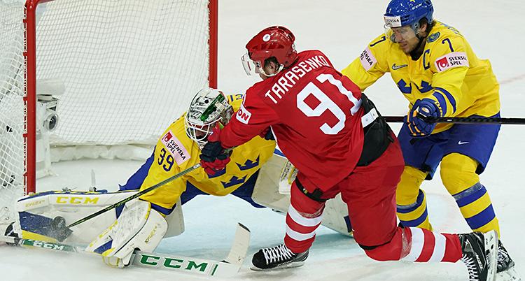Från en match i ishockey. En spelare i det ryska laget är vid Sveriges mål. Den ryska spelaren försöker göra mål. Den svenska målvakten och en annan svensk spelare försöker stoppa ryssen.