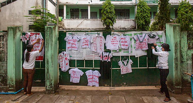 Två kvinnor hänger upp tröjor på en vägg. På tröjorna står det budskap.