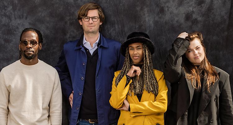 Fyra personer står mot en mörk vägg. De tittar in i kameran.