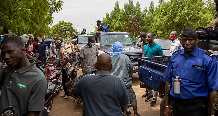 Bilden är från en gata i staden Bamako i Mali. Det är fullt av bilar och människor på gatan. Bredvid gatan växer buskar och träd.