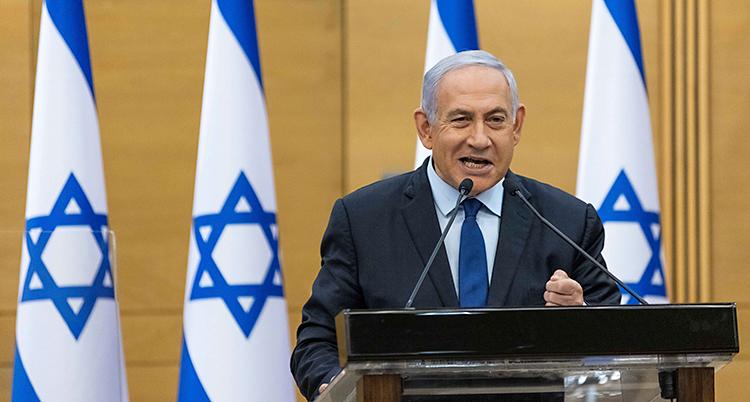 Netanyahu står och pratar i riksdagen. Han står i en talarstol och pratar i en mikrofon. Han har grått hår och kostym. I bakgrunden finns Israels flagga.