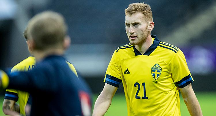 Bilden är tagen på en fotbollsplan. Dejan Kulusevski går på planen. Han har på sig Sveriges gula tröja.