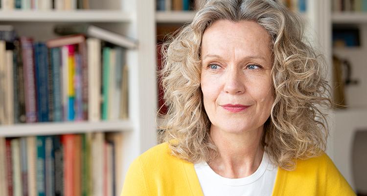 Åsa Wikforss i gul kofta framför en bokhylla.