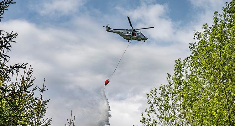 En helikopter flyger i luften. Från helikoptern hänger en lina. I slutet av linan finns en behållare som släpper ner vatten på marken.