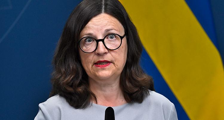 Anna Ekström framför en blågul vägg på en presskonferens.
