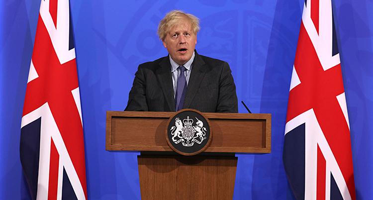Boris Johnson står och håller ett tal. Han står i en talarstol och pratar i en mikrofon. Han har spretigt ljust hår och en kostym. Bredvid står Storbritanniens flagga.