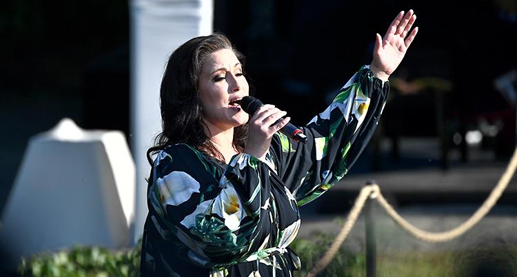 Lisa Nilsson står på en scen. Hon sjunger i en mikrofon och blundar med ögonen.