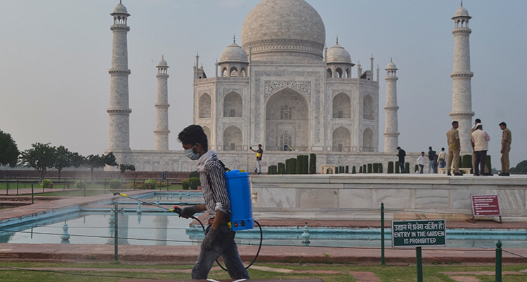 En man med munskydd och maskin på ryggen sprutar och rengör framför byggnaden Taj Mahal.