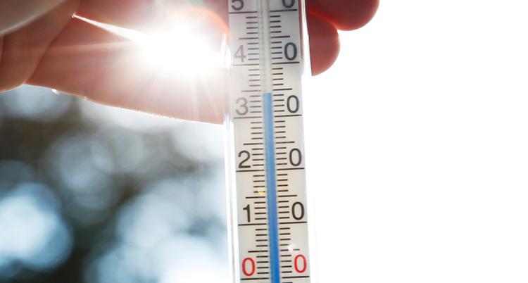 En hand håller en termometer som visar på över 30 grader.