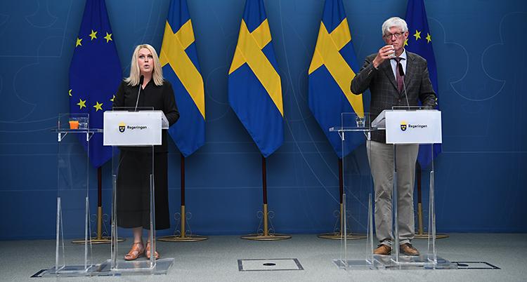 De står i varsin talarstol. Lena Hallengren står till vänster. Johan Carlson står till höger. Bakom dem finns svenska flaggor.
