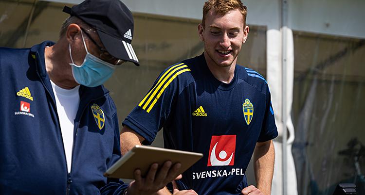 Från en träning med Sverige. Dejan Kulusevski är glad. Bredvid honom står en man med munskydd.