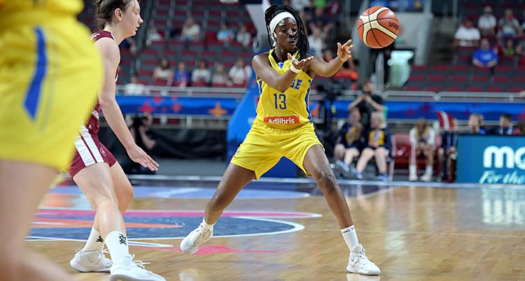 Från en match i basket. Bollen är i luften. Binta Drammeh är på väg att ta emot den. Hon har gula kläder.