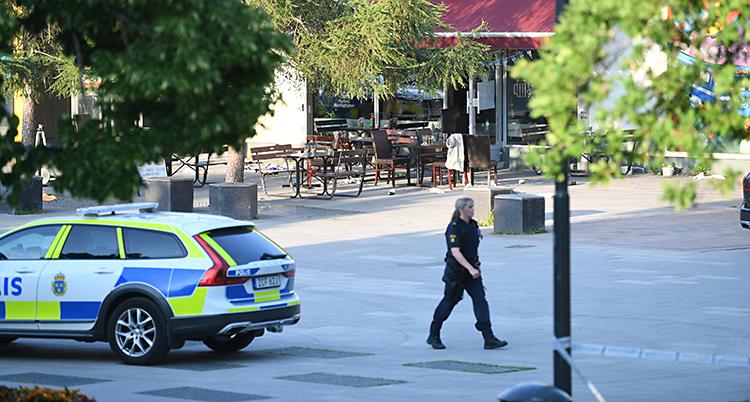Från Sätra centrum. Där står en polisbil och en polis går omkring. I bakgrunden syns en pizzeria som har en uteservering.
