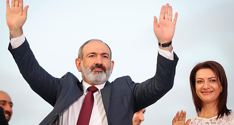 Han står och tackar de som röstat på honom. Han håller upp sina händer. Han har grått skägg och kostym. Bredvid honom står en kvinna med mörkt hår och vita kläder.