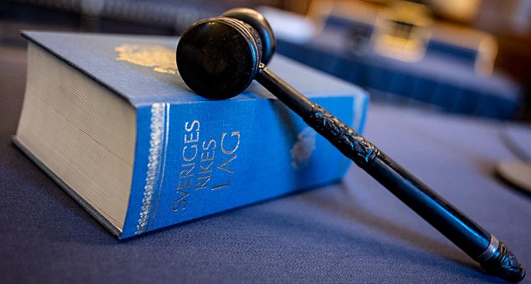 En lagbok och en domarklubba. Bilden är tagen i en domstol.