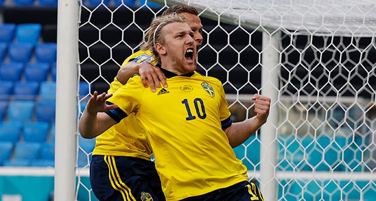 Från en match i fotboll. Emil Forsberg har gjort mål på straff. Han skriker och jublar. Han blir kramad bakifrån av en annan svensk spelare.