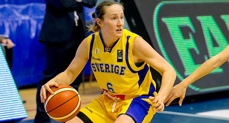 Från en match i basket. Frida Eldebrink har bollen. Hon har gula kläder med blå detaljer. Det står Sverige i blått på bröstet.