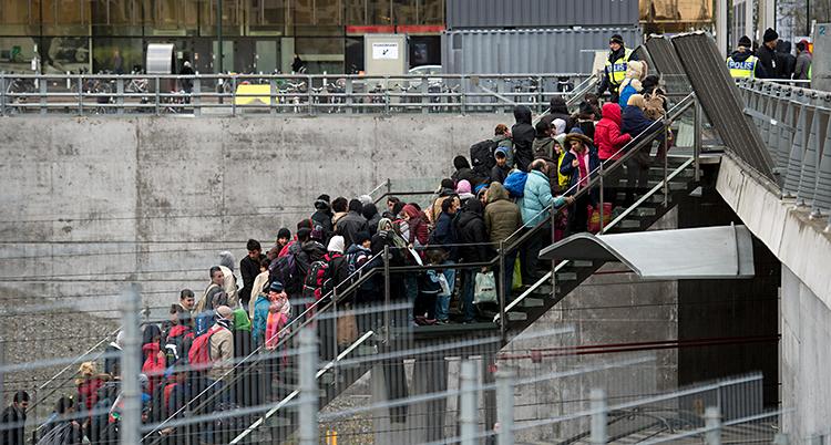 Bilden är tagen vid en tågstation. Människor går uppför en trappa. Längst upp i trappan står poliser.
