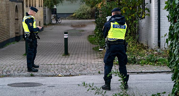 En gata i Malmö. Två poliser står på gatan.
