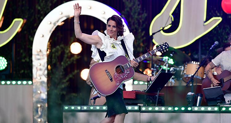Hon står på en scen med en gitarr.
