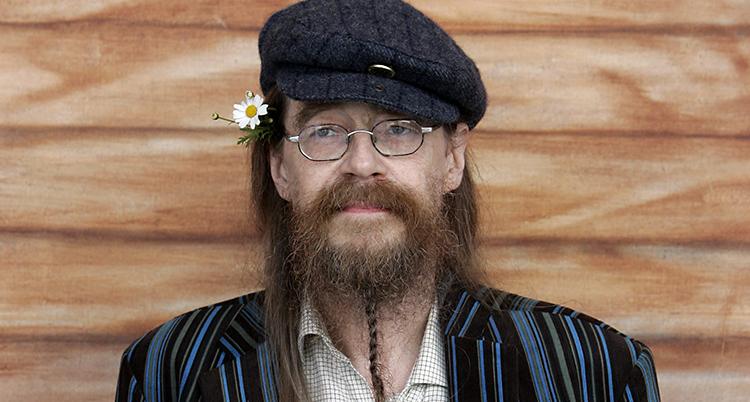 Han står vid en vägg. Han har långt hår, skägg och glasögon. Han har en keps på huvudet och en blomma bakom örat.