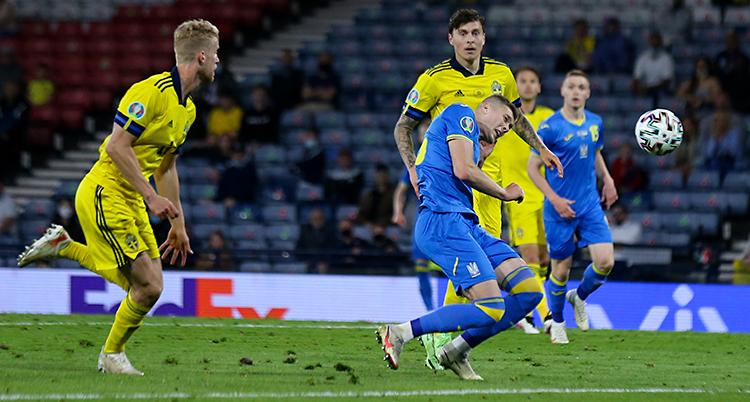 Från en match i fotboll. En spelare i blå kläder nickar bollen. Två spelare i gula kläder är bakom honom.