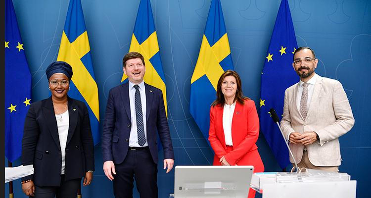 Fyra politiker står bredvid varandra. Bakom dem syns Sveriges flagga.