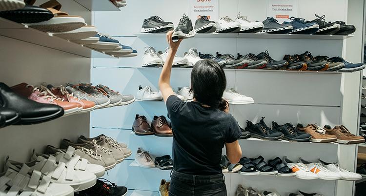 En person lyfter upp en sko på en skohylla i en skoaffär.