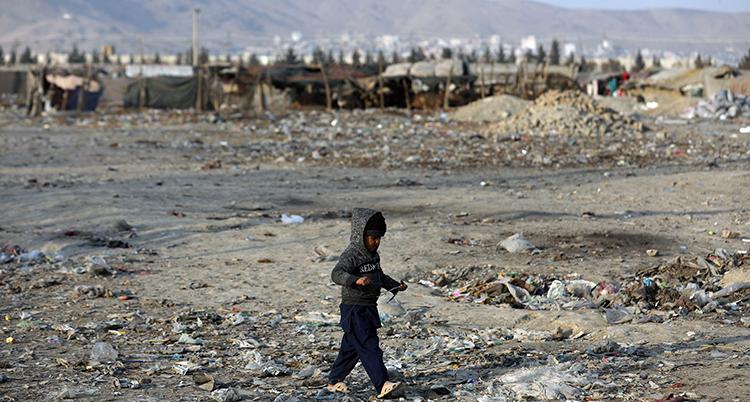 ett barn går framför ett läger för flyktingar i Afghanistan.