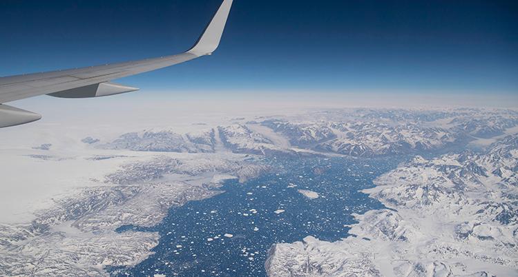 Vit is som ses från luften. Blå himmel och blått hav. En del av en flygplansvinge syns till vänster i bild