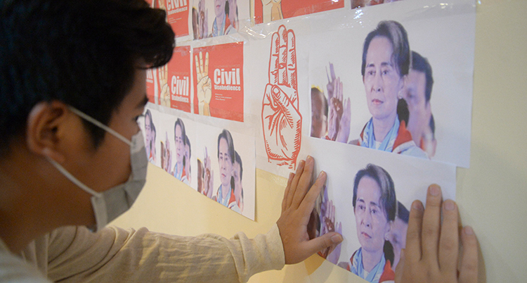 En man med munskydd sätter upp en bild på en vägg.