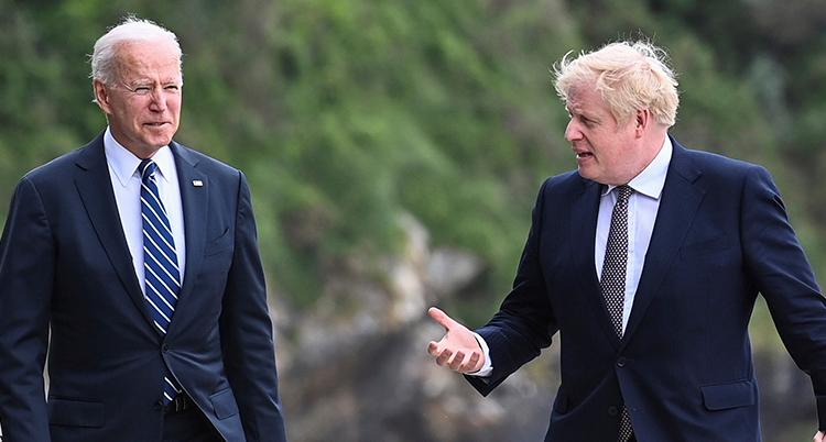 De båda går bredvid varandra. De har slips och mörk kavaj. Johnsson pratar och gör en gest med ena handen.