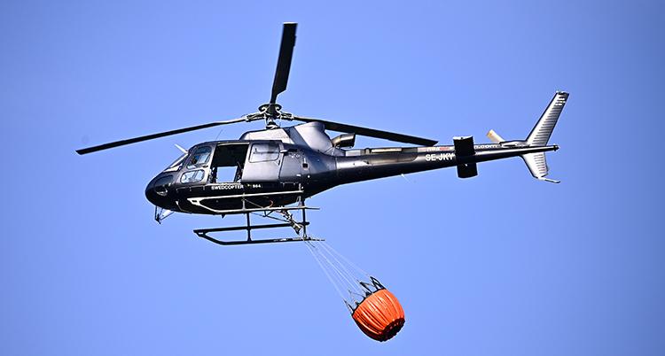 En helikopter i luften. Under den hänger en stor röd säck.