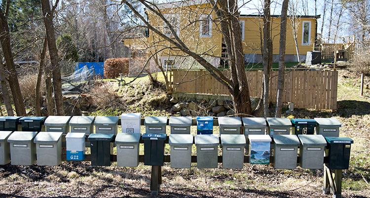 En rad med brevlådor. Bakom dem ett gult hus en bit bort.