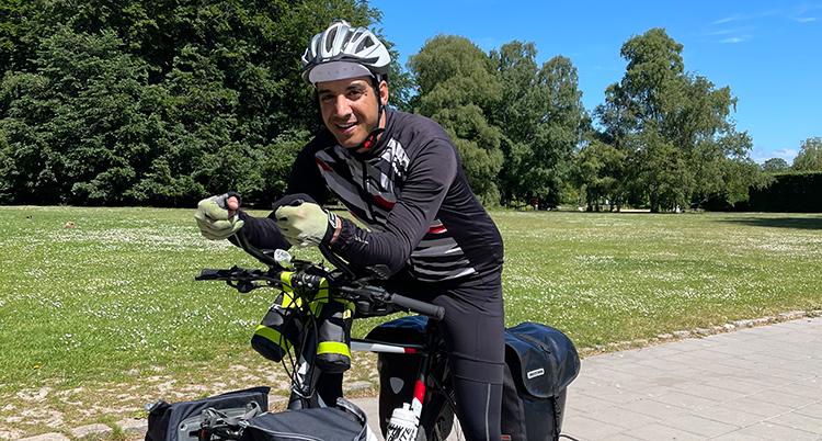 Han har svart cykelhjälm, svarta kläder och håller i styret på en cykel med händer i handskar. Han står utomhus. Det är grönt omkring honom.