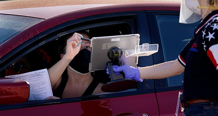 Hon sitter i en bil, har svart munskydd. Genom det öppna fönstret sträcker en person in en surfplatta som kvinnan klickar på med en penna. Hon håller ett papper i andra handen.