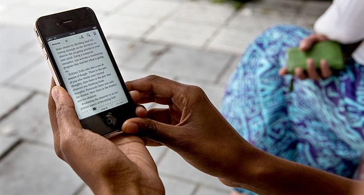 En kvinna läser en bok på sin mobiltelefon.
