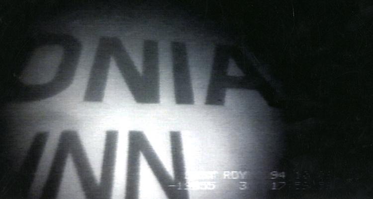 """En svartvit bild tagen under vattnet. Vi ser bokstäver på fartygets sida. Bokstäverna """"onia"""" och under """"inn"""""""
