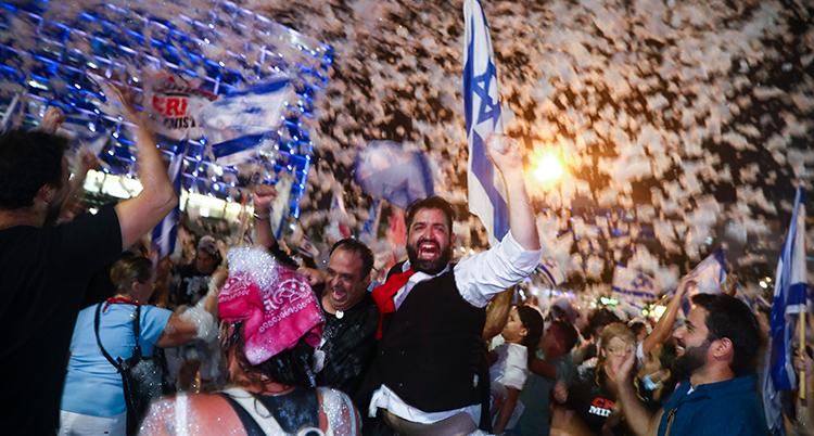 Det är kväll. Folk jublar. En man i väst och vit skjorta skrattar och håller upp en knuten hand. Bakom honom Israels flagga.