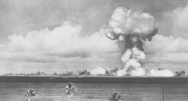En svartvit bild över ett hav med palmer i förgrunden. Ett gigantiskt svampformat moln syns i horisonten.