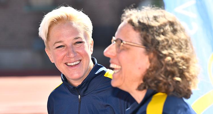 Hon har ljust kort hår och ler in i kameran. I förgrunden syns profilen av en kvinna med mörkt vågigt hår och glasögon. De är på en idrottsarena utomhus.