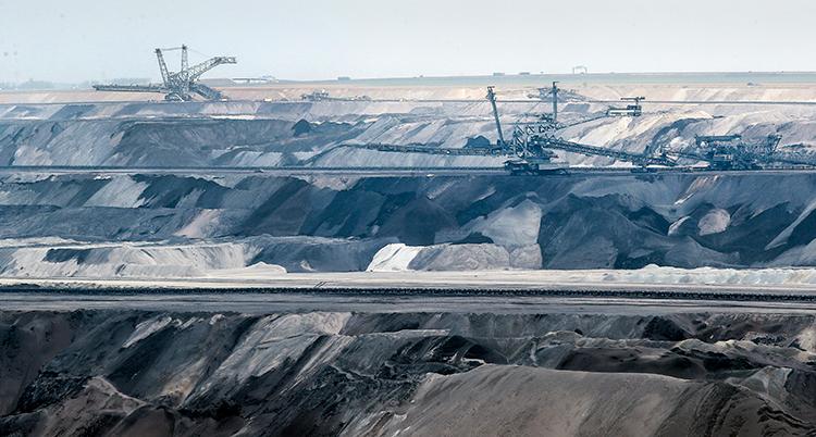 en vybild på kolutvinning i Tyskland. Grå berg och stora maskiner.