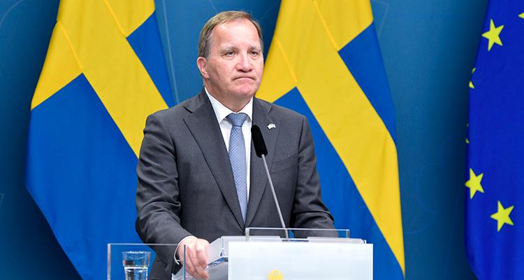 Löfven står framför svenska flaggor. Han ser besviken ut. Mungiporna är neråt.