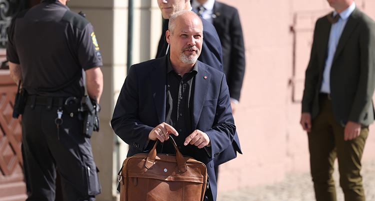 Johansson är på väg är utomhus. Han har en portfölj i handen.