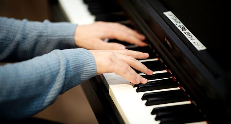 Två händer spelar på ett piano.