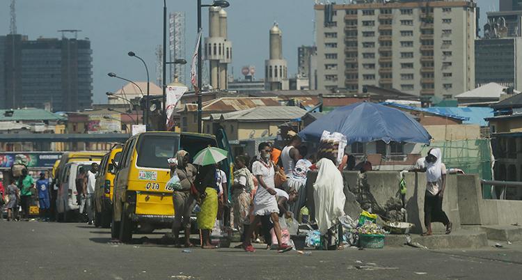 Människor på en gata. I bakgrunden höga hus. Det står några gula taxibilar på gatan.