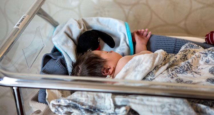 En nyfödd bebis ligger i en genomskinlig låda på ett sjukhus.