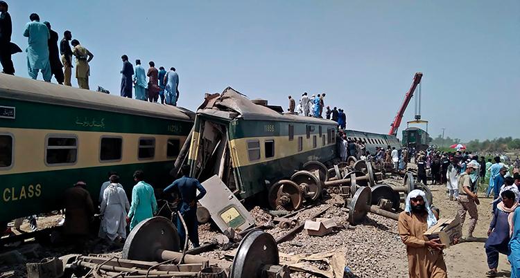 Ett trasigt tåg står på ett spår. Lösa delar av tåget ligger bredvid. Människor syns runt tåget.