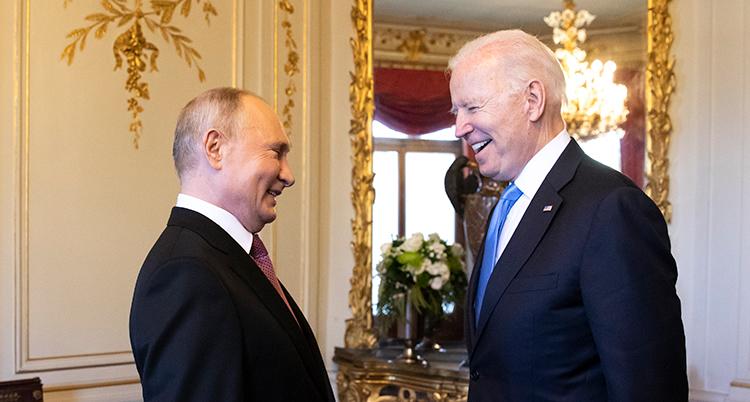 De två ledarna står nära varandra. De tittar på varandra och skrattar.